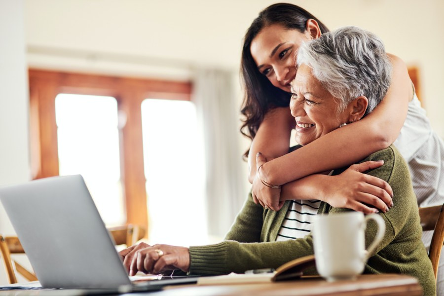 woman in her 20s to 30s embracing her elderly mother from behind as she works on her laptop.
